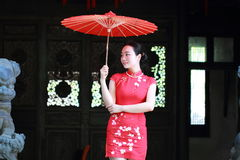 Happy Chinese bride in red cheongsam at traditional wedding day. Chinese bride in red cheongsam at wedding day , hold red oiled paper umbrella, climb stairs Stock Photo