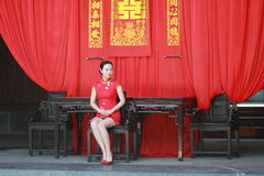 Happy Chinese bride in red cheongsam at traditional wedding day. Chinese bride in red cheongsam at wedding day , hold red oiled paper umbrella, climb stairs Royalty Free Stock Photography