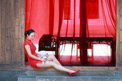 Happy Chinese bride in red cheongsam at traditional wedding day. Chinese bride in red cheongsam at wedding day , hold red oiled paper umbrella, climb stairs Stock Image