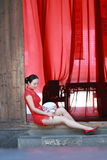 Happy Chinese bride in red cheongsam at traditional wedding day. Chinese bride in red cheongsam at wedding day , hold red oiled paper umbrella, climb stairs Stock Images