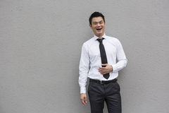 Happy Chinese business executive laughing and standing in front Stock Photo