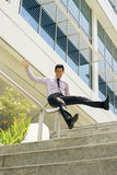 Happy Chinese Businessman Going Downstairs Sliding On Rail. Young and happy chinese businessman sliding downstairs on rails of office staircase. The man enjoys Stock Photography