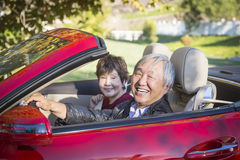 Happy Chinese Couple Enjoying An Afternoon Drive in Their Conver Stock Image