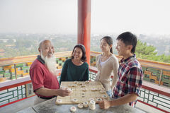 Happy Chinese Family Playing Chinese Chess (Xiang Qi) Stock Photography