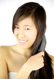Happy Chinese girl brushing long hair Royalty Free Stock Photos