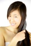 Happy Chinese girl brushing long hair Royalty Free Stock Photos