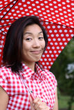 Happy Chinese girl with dotted umbrella and shirt. Attractive young Chinese girl outdoors with dotted red umbrella and striped shirt Stock Photography
