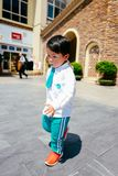 Chinese boy on the street in school uniform. Happy chinese kid join out door activity on the street royalty free stock photography
