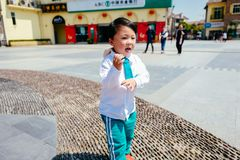 Chinese boy on the street in school uniform. Happy chinese kid join out door activity on the street royalty free stock image