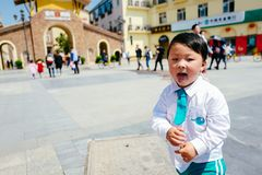 Chinese boy on the street in school uniform. Happy chinese kid join out door activity on the street stock photos