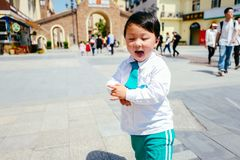 Chinese boy on the street in school uniform. Happy chinese kid join out door activity on the street royalty free stock photo