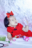 Happy Chinese little baby in red cheongsam have fun Stock Photo