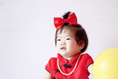 Happy Chinese little baby in red cheongsam play yellow balloon Stock Image