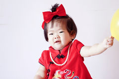 Happy Chinese little baby in red cheongsam play yellow balloon Royalty Free Stock Photos