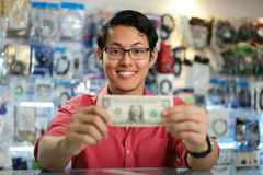 Happy Chinese Man Showing First Dollar Earning In PC Shop. Young asian shop owner in computer store, showing his first dollar to the camera and smiling. Focus on Royalty Free Stock Photos