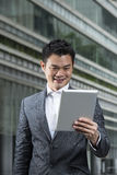 Happy Chinese man with a tablet computer. Stock Photos