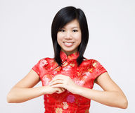 Happy Chinese New Year. Oriental girl wishing you a happy Chinese New Year. Cheongsam also known in English as a mandarin gown, is formal wear for important