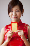 Happy Chinese New Year. Oriental girl in cheongsam wear holding a Chinese red packet wishing you happy Chinese New Year Royalty Free Stock Photography