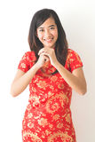 Happy Chinese new year. Asian woman wearing red dress. With gesture of congratulation standing over white background