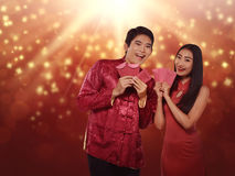 Happy chinese new year concept. Asian couple in cheongsam suit holding angpao. Happy chinese new year concept