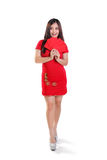Happy Chinese New Year girl full length isolated. Full body portrait of happy young Asian female model wearing cheongsam dress, holding red envelopes and looking Stock Photo