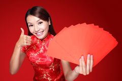 Happy chinese new year. Smile asian woman holding red envelope isolated on red background