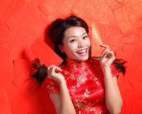 Happy chinese new year. Smile woman lying on red envelope bed, high angle view