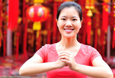 Happy chinese new year. Young asian woman folded hands wishing you a happy chinese new year