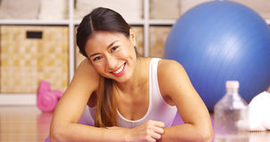 Happy Chinese woman lying on yoga matt Stock Image