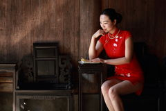 Happy Chinese woman in red cheongsam read book. Chinese bride in red cheongsam at wedding day , hold red oiled paper umbrella, climb stairs. significant day Royalty Free Stock Images