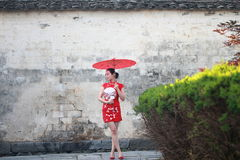 Happy Chinese woman in red cheongsam tour at ancient town. Chinese bride in red cheongsam at wedding day , hold red oiled paper umbrella, climb stairs Stock Photos