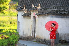 Happy Chinese woman in red cheongsam tour at ancient town Stock Images