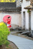 Happy Chinese woman in red cheongsam tour at ancient town Stock Photo