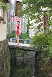 Happy Chinese woman in red cheongsam tour at ancient town Stock Photos