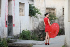 Happy Chinese woman in red cheongsam tour at ancient town Royalty Free Stock Images