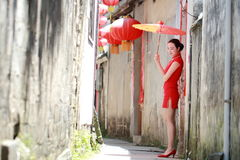 Happy Chinese woman in red cheongsam walk in the alley. Chinese bride in red cheongsam at wedding day , hold red oiled paper umbrella, climb stairs. significant Stock Image