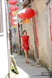 Happy Chinese woman in red cheongsam walk in the alley Stock Image