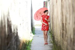Happy Chinese woman in red cheongsam walk in the alley Royalty Free Stock Photography