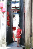 Happy Chinese woman in red cheongsam walk in the alley Royalty Free Stock Photos