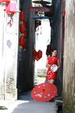 Happy Chinese woman in red cheongsam walk in the alley Royalty Free Stock Image