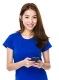 Happy Chinese woman texting with smartphone Royalty Free Stock Images