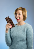 Happy chocolate addict woman holding big bar mouth stained and crazy excited face expression Stock Photos