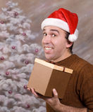 Happy Christmas. A happy man holding a Christmas present and smiling in front of a hand painted xmas background Royalty Free Stock Image