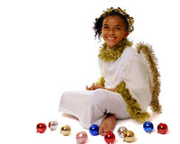 Happy Christmas Angel. Happy biracial girl dressed as an angel sitting among scattered Christmas bulbs royalty free stock photo