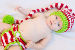 Happy Christmas Baby!. Baby wearing red white and green striped knit hat and diaper cover Stock Photography