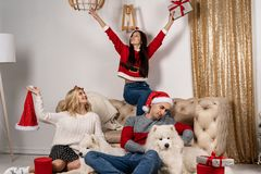 Happy christmas celebrating of young people with dogs and gifts stock image