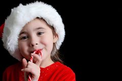 Happy Christmas child with Santa hat and Candy cane over black b Royalty Free Stock Photo