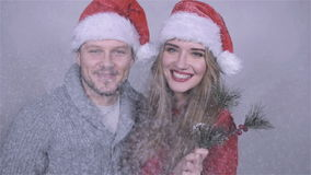 Happy Christmas couple blowing snow over white background. stock video