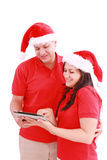 Happy Christmas couple looking a tablet computer Stock Photo