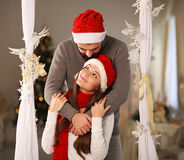 Happy Christmas couple in love at home. Happy Christmas couple in love in red hats at home Royalty Free Stock Images